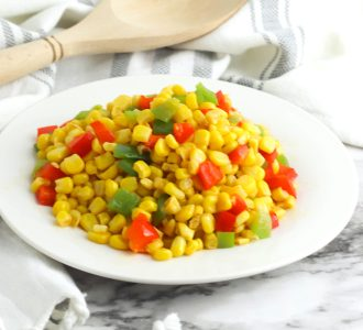 Fiesta Corn served on a round white plate with a wooden spoon in the background.