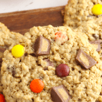 Close up of a Reese's Pieces Monster Cookie sitting on a stack of cookies.