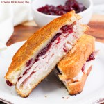 Turkey Cranberry Grilled Cheese sliced in half and laying on a white plate.