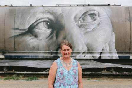 The-Wanderers-episode-Street-Artist -Guido-van-Helten_Manildra local MARIAN DUNCAN posing in front of a mural of her painted by GUIDO VAN HELTEN_credit Callie Marshall_I5A7240