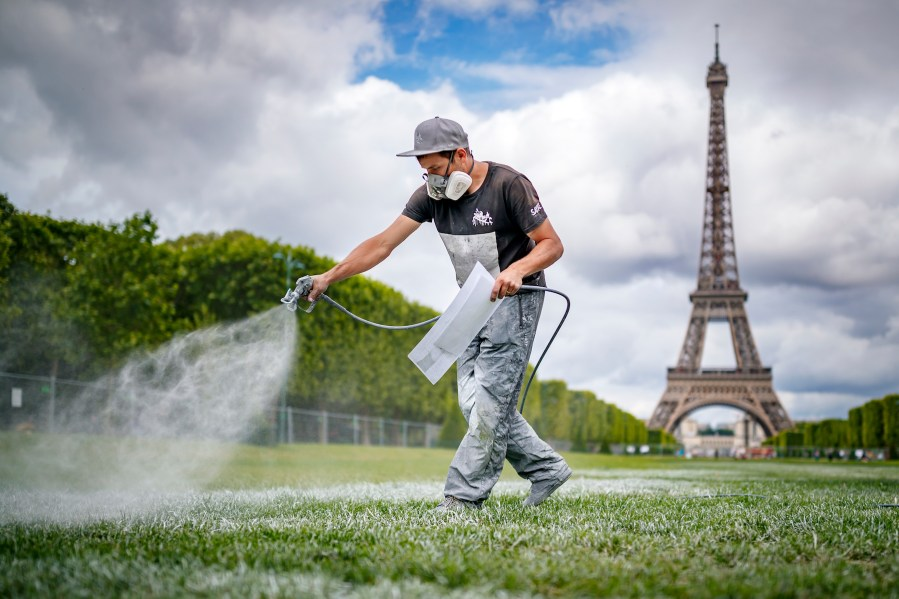 """French-Swiss artist Saype works on a giant biodegradable landart painting Monday June 10, 2019 on the Champ de Mars in front of the iconic Eiffel Tower in Paris, France. With an overall area of 15'000 square meters, the 600 meters long and 25 meters wide painting (likely one of the largest of its kind) was created using biodegradable pigments made out of charcoal, chalk, water and milk proteins. This art piece launches the worldwide project """"Beyond Walls"""" aiming at creating the longest symbolic human chain around the world promoting values such as togetherness, kindness and openness to the world. (VFLPIX.COM /Valentin Flauraud)"""