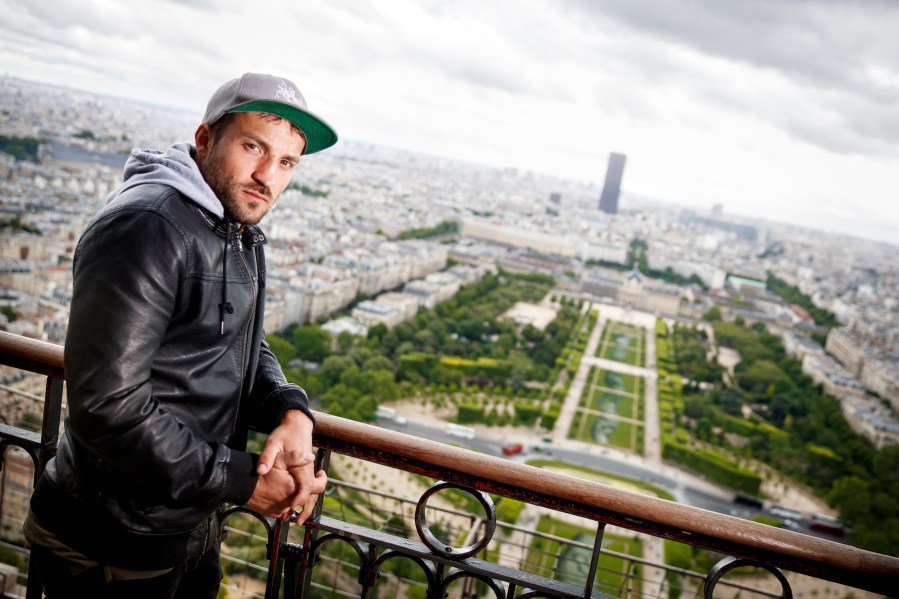 """French-Swiss artist Saype poses in front of his giant biodegradable landart painting on Tuesday June 11, 2019 on the Champ de Mars in front of the iconic Eiffel Tower in Paris, France. With an overall area of 15'000 square meters, the 600 meters long and 25 meters wide painting (likely one of the largest of its kind) was created using biodegradable pigments made out of charcoal, chalk, water and milk proteins. This art piece launches the worldwide project """"Beyond Walls"""" aiming at creating the longest symbolic human chain around the world promoting values such as togetherness, kindness and openness to the world. (VFLPIX.COM /Valentin Flauraud)"""