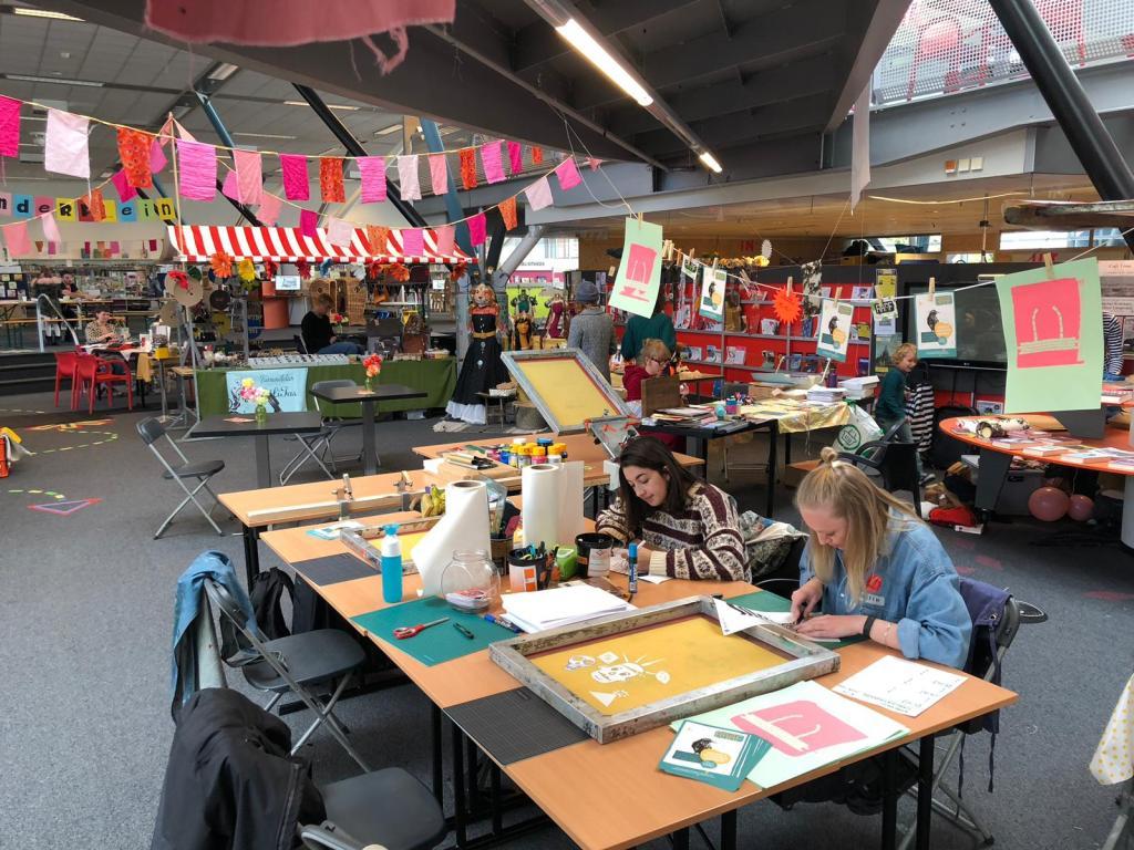 Raaf bij Marche Hoezee. Een grote kleurijke ruimte met workshop tafels