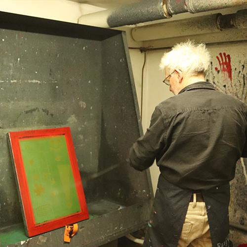 Man in spuitcabine met hogedrukspuit en zeefdruk raam