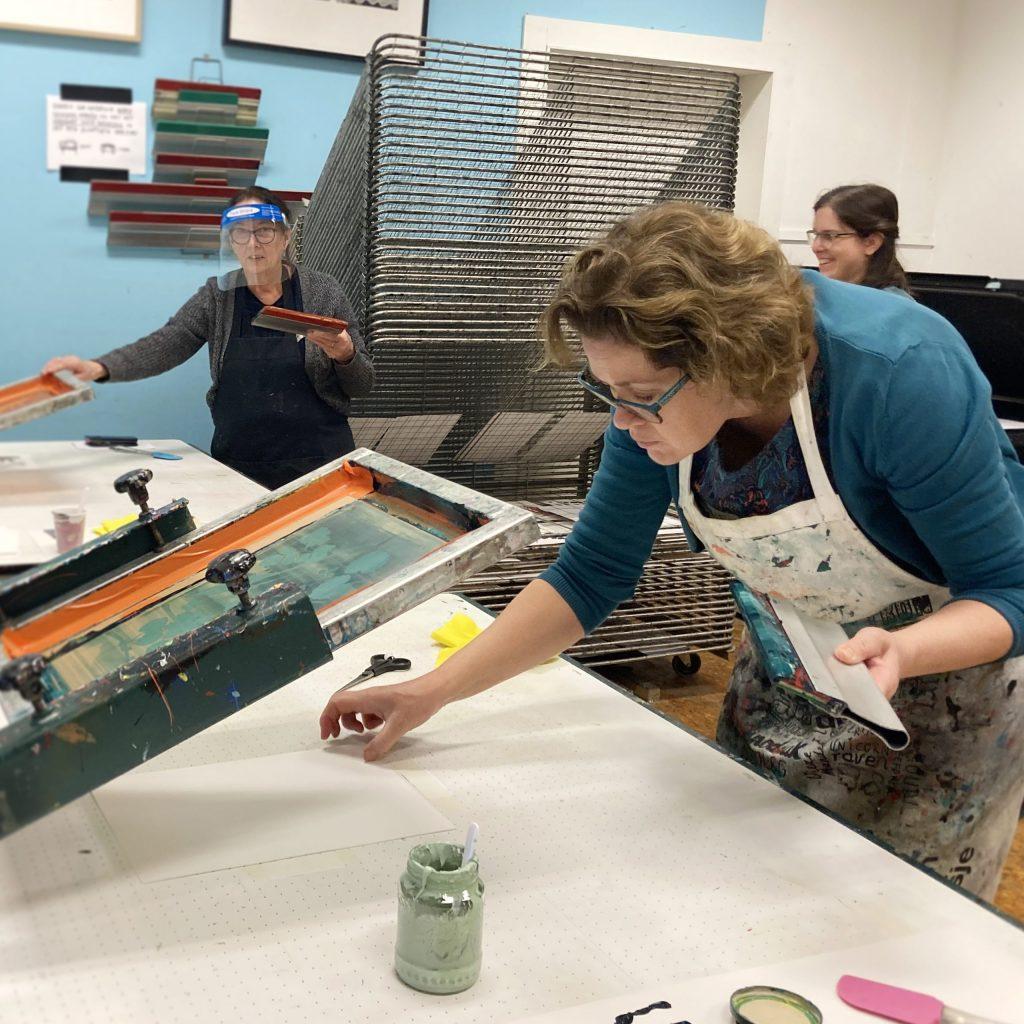 Vrouw in voorgrond legt een leeg papier onder een zeefdruk raam. Een rakel met verf in haar linkerhand. In de achtergrond kletsen twee vrouwen bij het droogrek.