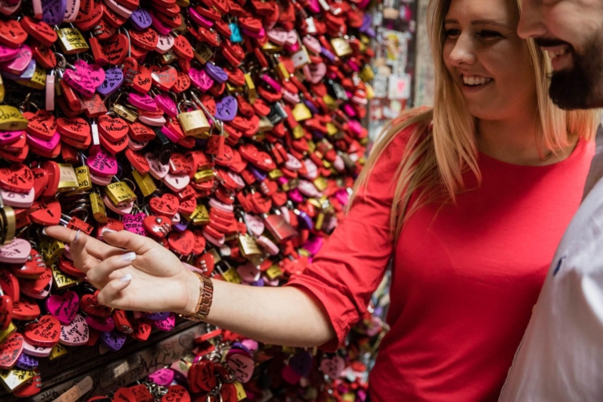 A romantic couple look at the love locks at Casa di Giulietta in Verona