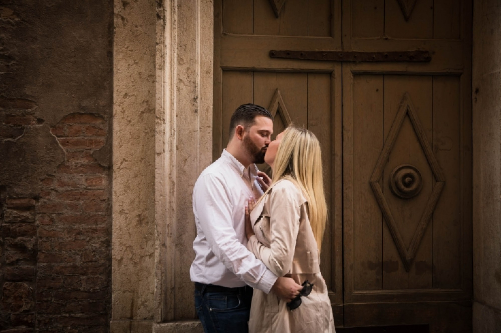 A couple in love kiss soon after arriving in Verona, Italy