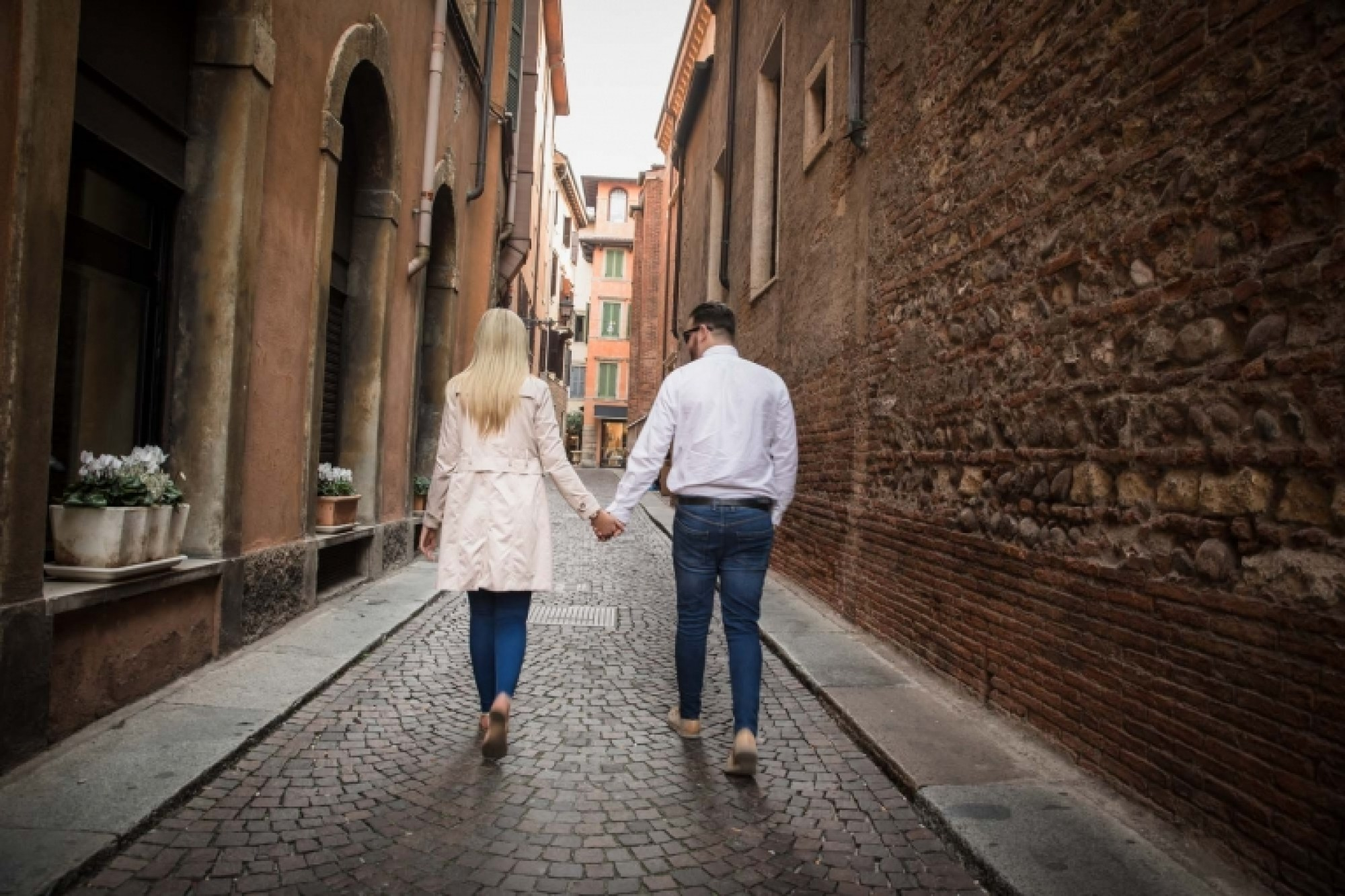 A couple in love hold hands through the back streets of Verona old town