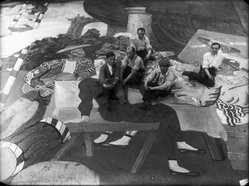 Pablo Picasso and scene painters sitting on the front cloth for Parade, photo by Lachmann