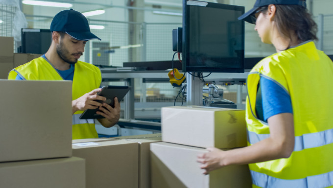 Post Sorting Center Worker Puts Cardboard Boxes on Belt Conveyor while Another Worker using Tablet PC.
