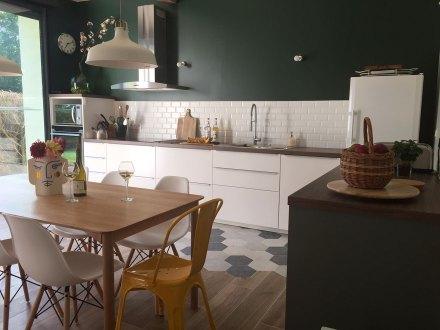 La Maison de Célestin, dans la cuisine. Grands meubles blancs mat, plan de travail sur mesure. Plaques à induction et hotte en inox, crédence en carrelage métro blanc