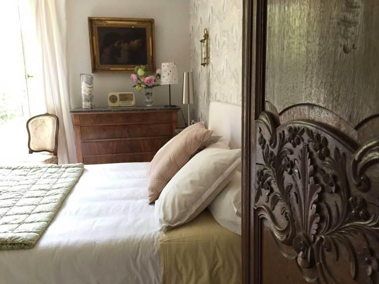 La chambre Oncle Roger de Grand Bouy, vue depuis l'entrée, gros plan sur les sculptures de l'armoire normande, vue sur le lit et la commode.