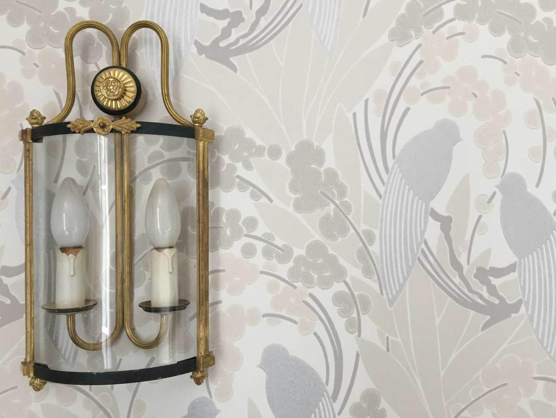 Chambre Oncle Roger de Grand Bouy, gros plan sur une applique ancienne à deux feux en laiton et verre bombé, papier peint Love birds d'Harlequin