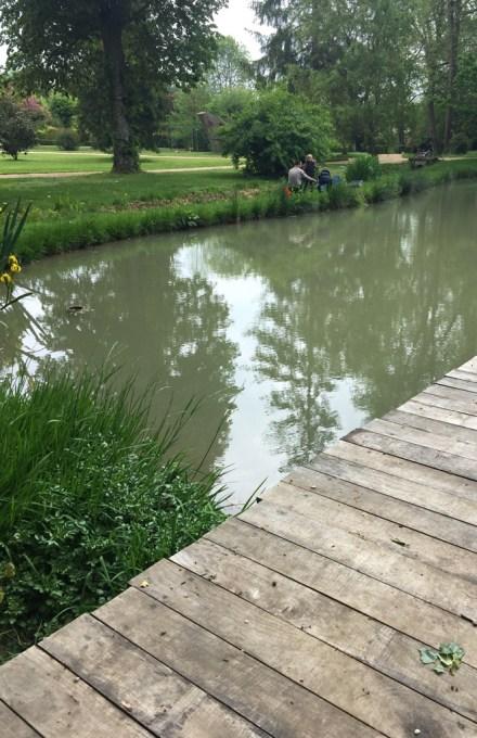Dans le parc de Grand Bouy, le ponton en planches de bois de l'étang, iris des marais et pêcheurs de gardons