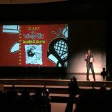 Jeff Kinney presenting on stage at author event.