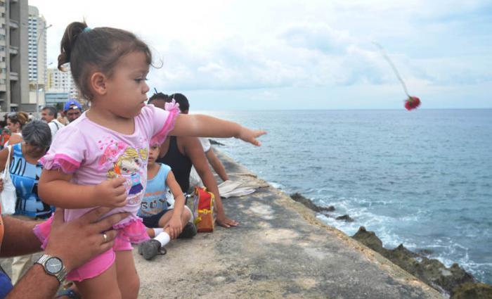 Niña echa una flor al mar por el aniversario 55 de la desaparición de Camilo Cienfuegos.