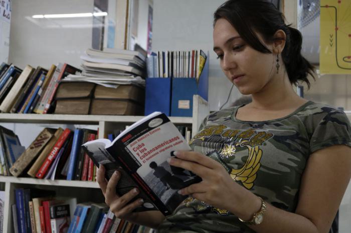 Estudiante de periodismo lee libro de Jesús Arboleya. Cuba y los Cubanoamericanos. El fenómeno migratorio cubano.