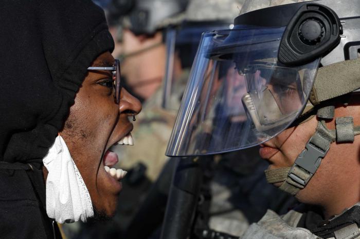 Un manifestante y un agente de la Guardia Nacional se enfrentan en la calle, en Minnesota. Foto: AP