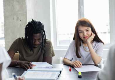 diverse students doing homework together in classroom