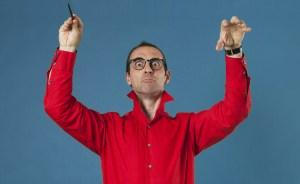 un grand magicien ou chef d'orchestre rouge et bleu