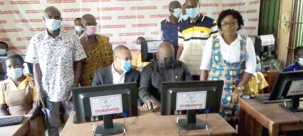 • Mr Michael Okyere Kofi Baafi (seated right), MP for New Juaben South, and Mr Mamadou Ly (seated left), Managing Director of the Nyonkopa Cocoa Buying Company Limited, demonstrating how the pupils should operate the computers at Densuano