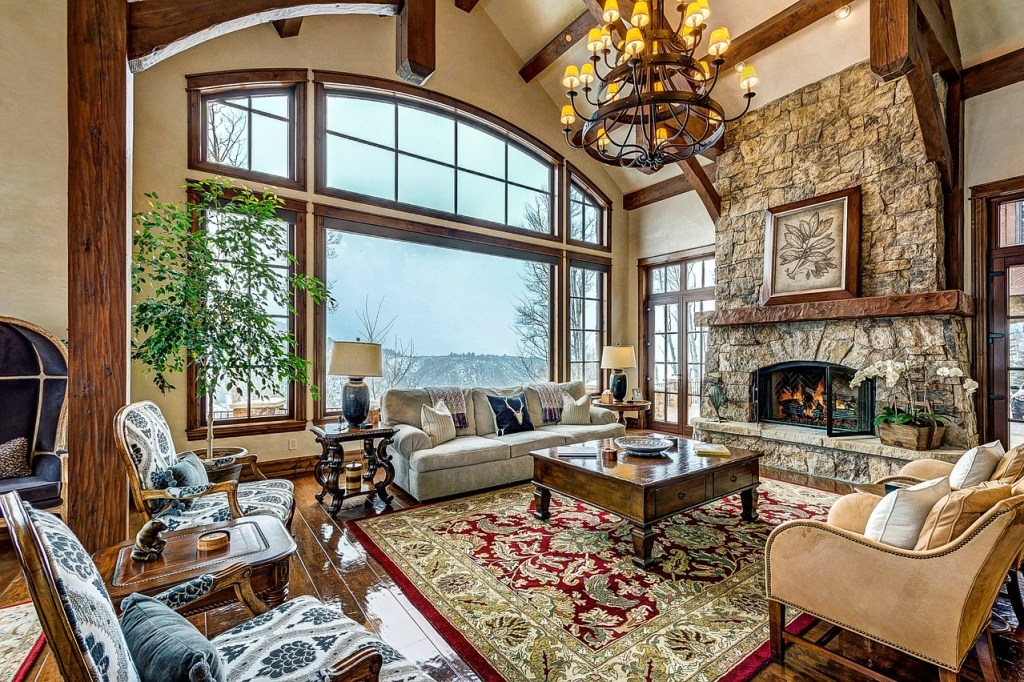 cool living room with fireplace and rug and wood coffee table also chandelier