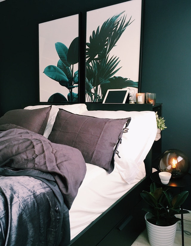 dark bedroom with two panel painting of palm plant