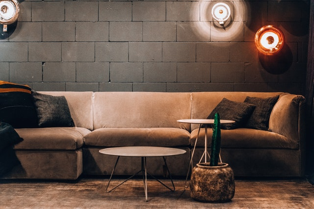 empty sofa beside wall and round lamps