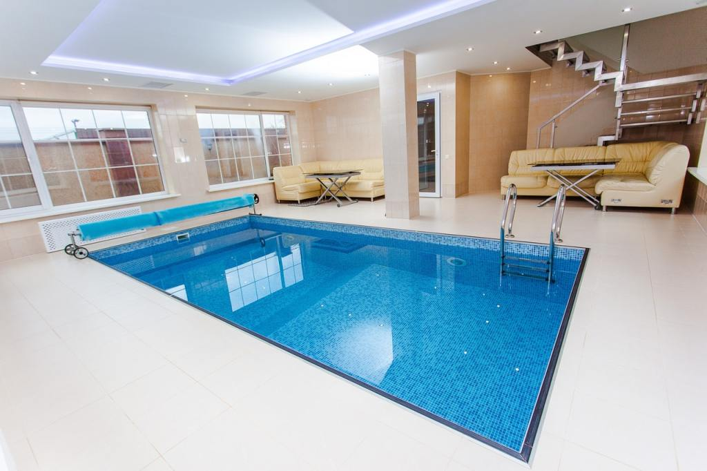 swimming pool area with ceiling lighting and sofa