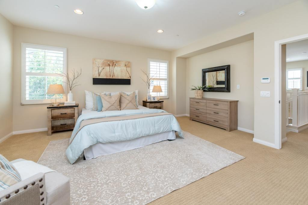 bright bedroom with wall pictures decor and rug also bedside table