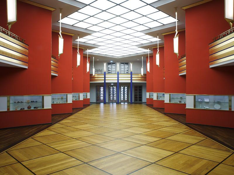 Veranstaltungsraum vom GRASSI Slam: die Pfeilerhalle im GRASSI: rote Säulenwände mit Vitrinen, Parkettboden, Oberlichter
