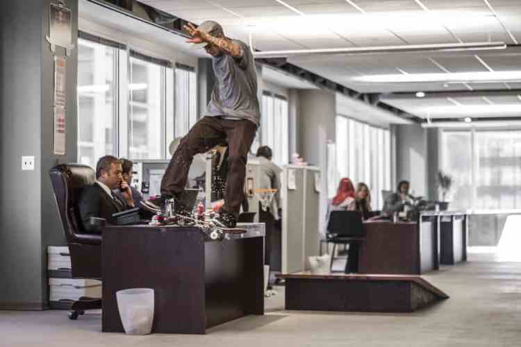 Ryan Sheckler executes a Frontside Lipslide on a desk in the Red Bull Daily Grind office