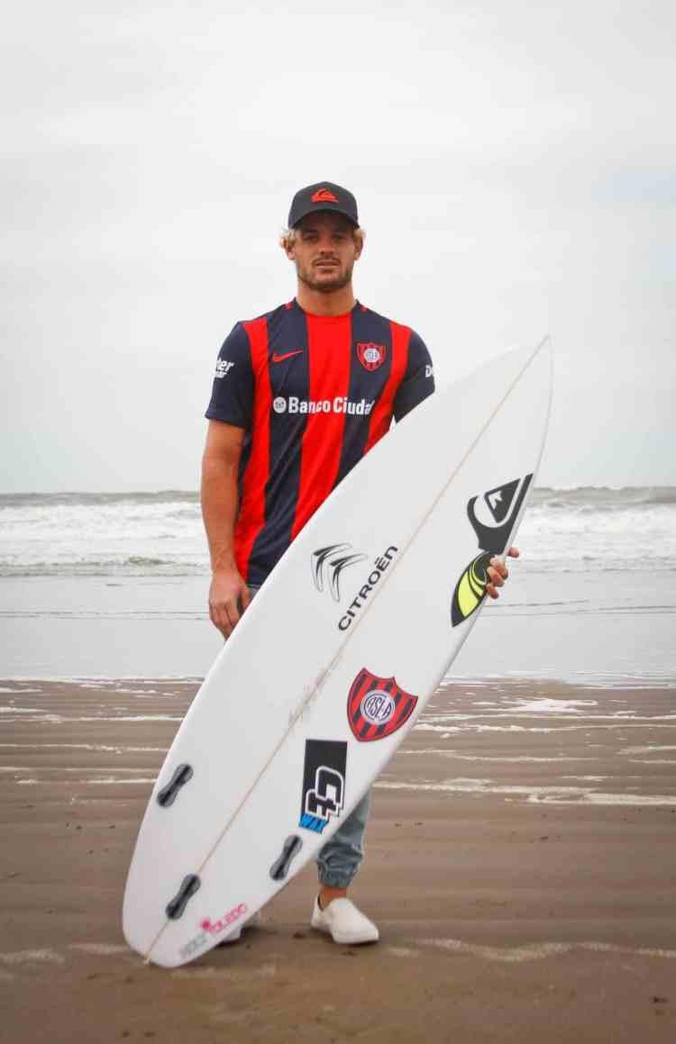Santi, la camiseta, la tabla con el escudo y el mar de fondo. Sus pasiones juntas.
