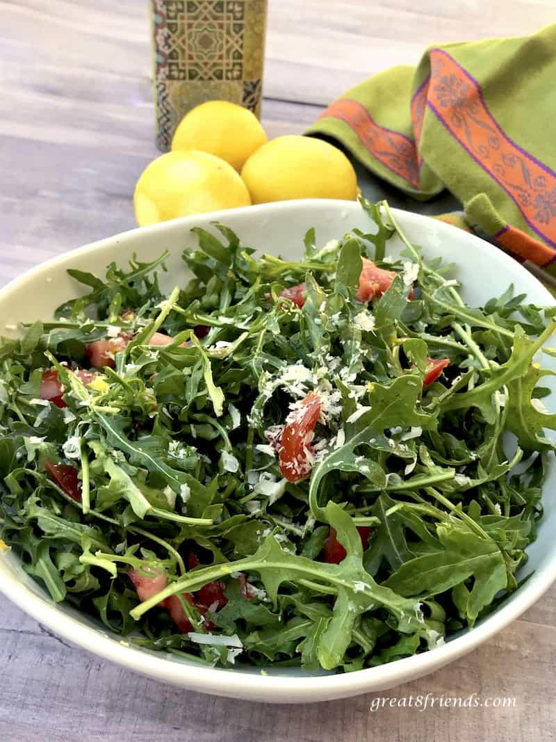 Arugula Salad with Lemon Parmesan Dressing in bowl with zested lemons and green and orange towel.