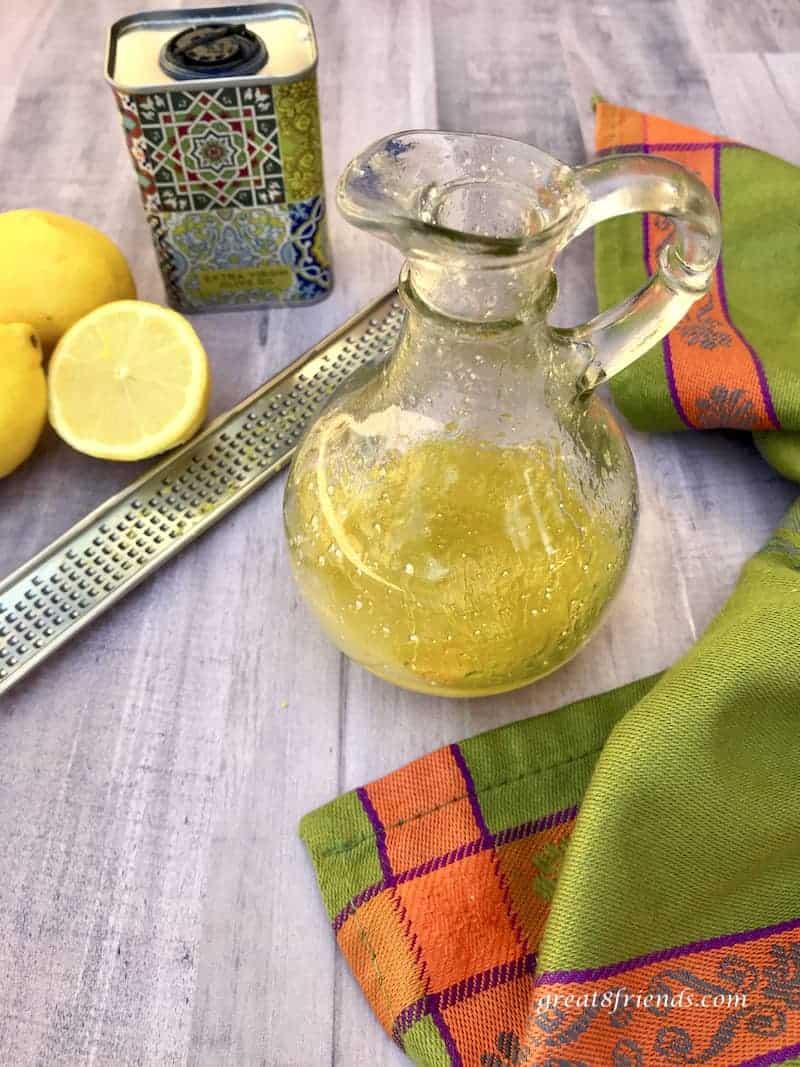 Lemon Parmesan Dressing in glass cruet with lemons, zester and olive oil.