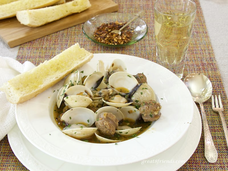 Clams with Hot Italian Sausage in bowl with bread, hot pepper, white wine and spoon