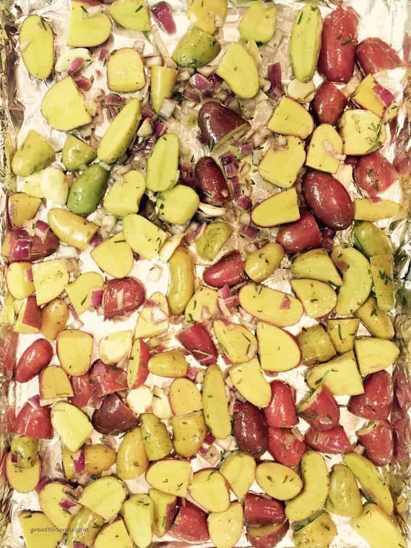 Cut up and seasoned potatoes on baking sheet.