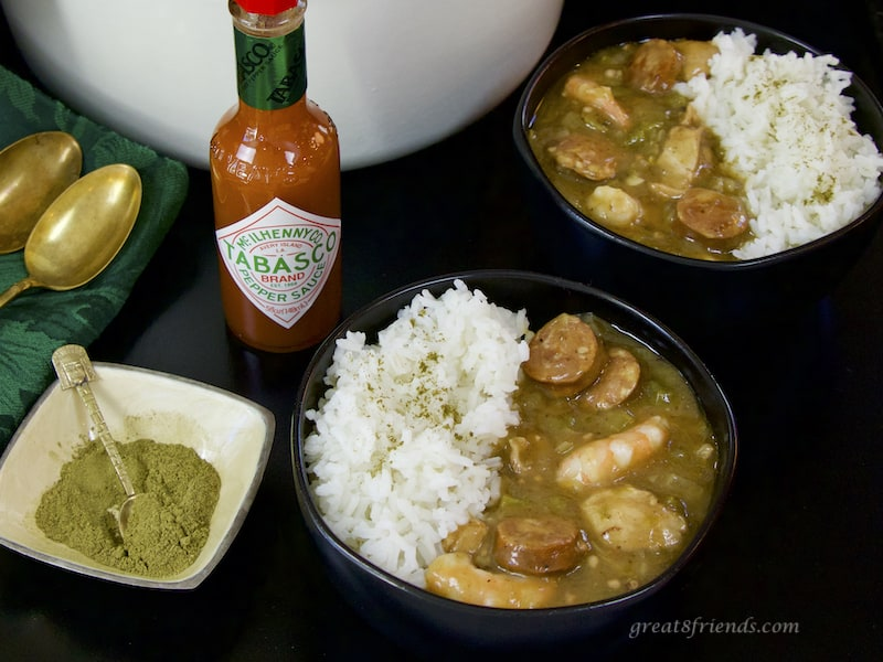 Two bowls of Sausage Shrimp and Chicken Gumbo with rice, tabasco, and filet powder