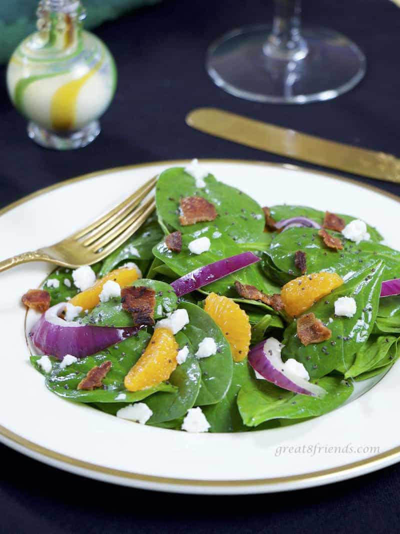 Spinach Salad with Poppy Seed Dressing and orange slices on a plate with a fork.