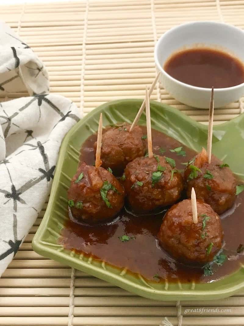 Five Hawaiian Meatballs on a green dish with toothpicks in each for eating and a bowl of extra sauce on the side.