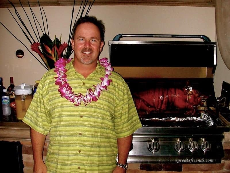 A man posing with a whole pig in the background roasting on a spit on a backyard grill.