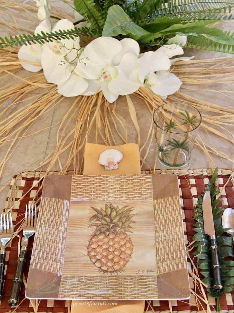 Place setting using for a Luau dinner party using pineapple plastic plates and orchids as the centerpiece.