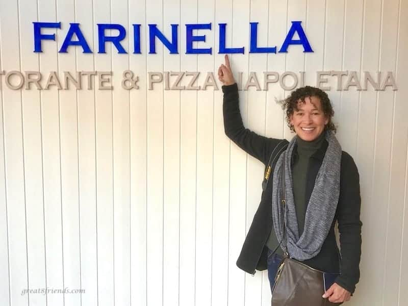 A woman pointing to the word Farinella on a wall.