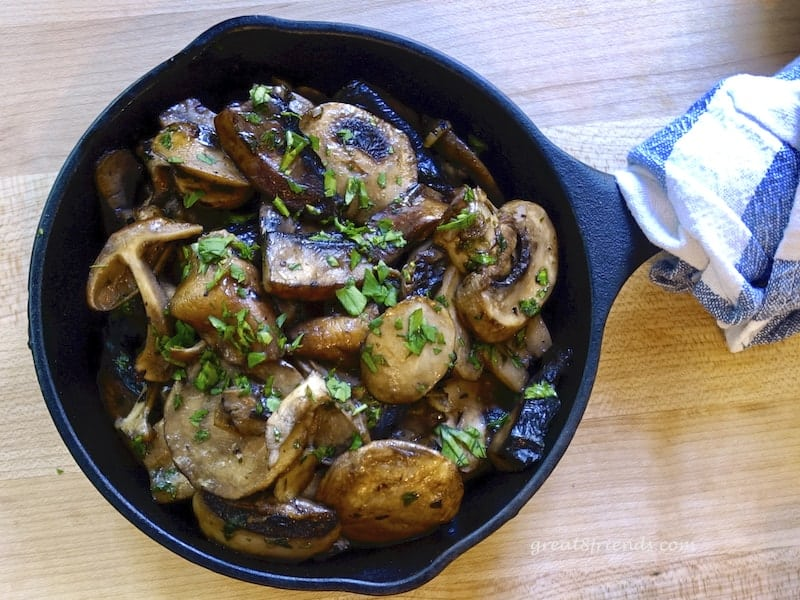 Overhead shot of Mushrooms in Garlic Sauce in a cast iron skillet.