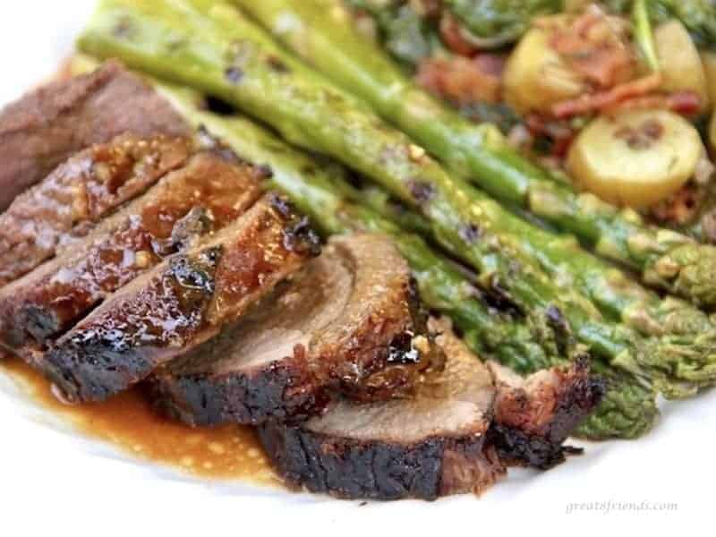 Marinated and butterflied leg of lamb sliced and served with sauce and grilled asparagus and bacon vinaigrette potato salad.
