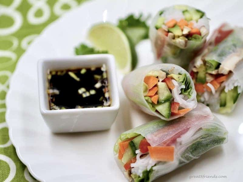 Cut fresh spring vegetable rolls served with a dipping sauce.