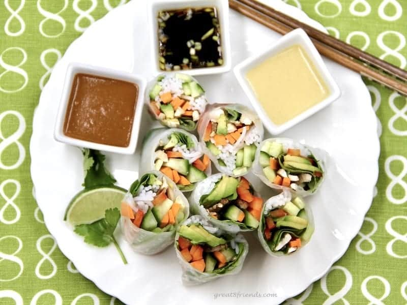 Overhead view of veggie rolls cut in half served with three dipping sauces.