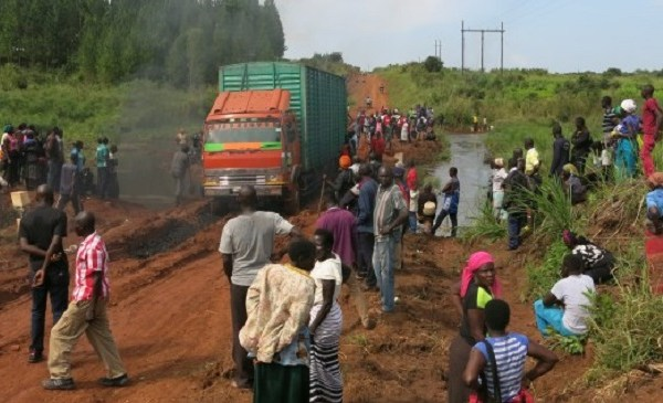Large truck stuck in mud on Ugandan road. Crowd of people stand nearby.