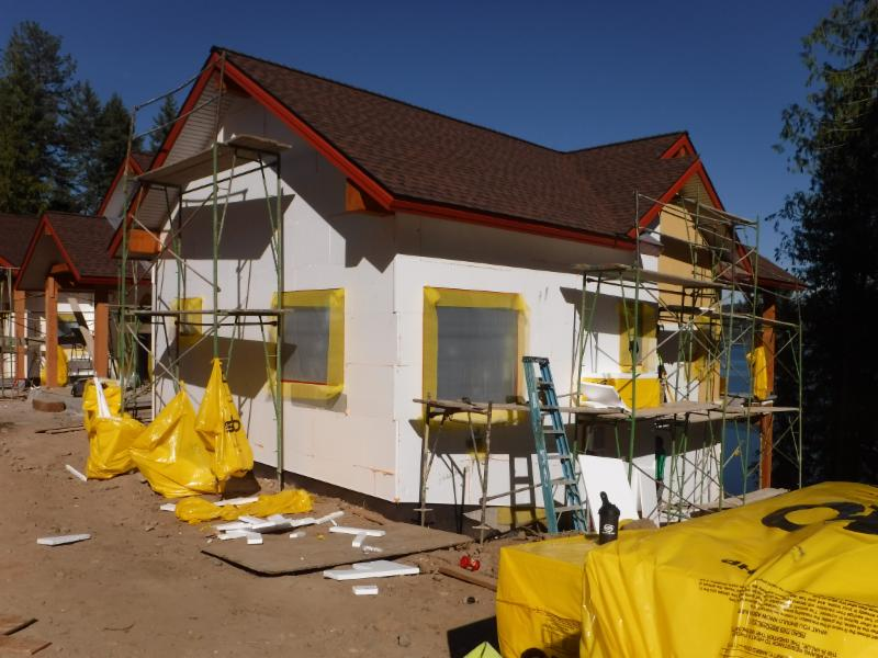The exterior walls are wrapped with rigid foam insulation board  to seal the home against the freezing winds.