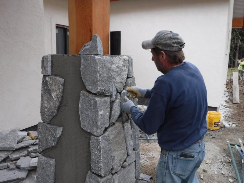 The mason expertly applies real quarried thin cut stone   over all the column bases.